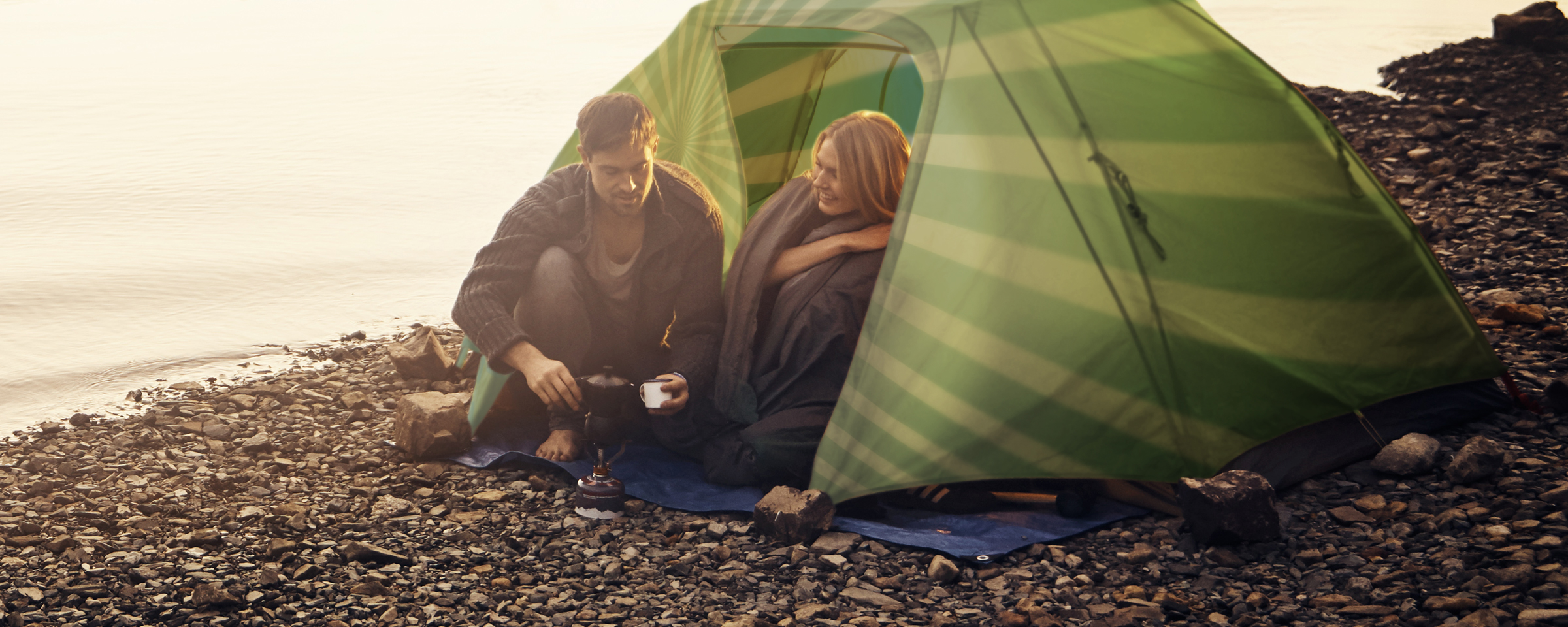 man and women sitting in camping tent by a lake
